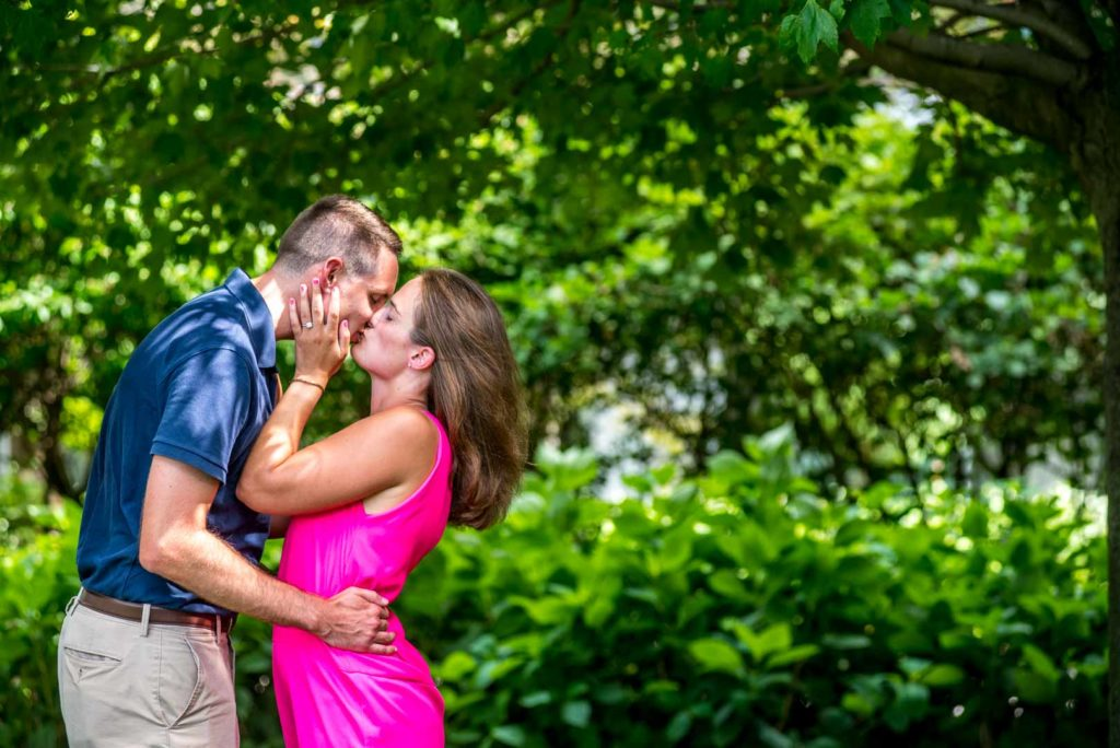 engagement kissing photo with green background