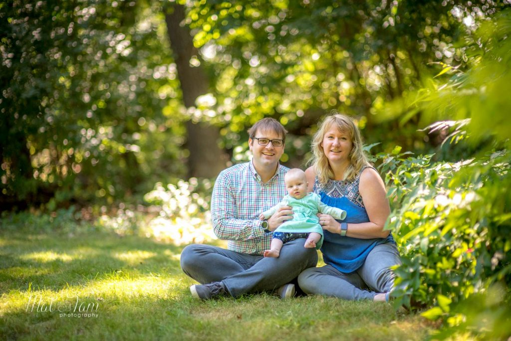 4 month old girl photos session at shannon beach in Winchester, MA with parents. Family photo. With dad and Mum. sitting down shot. Laughing